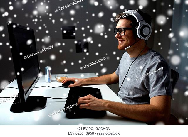 technology, gaming, entertainment, let's play and people concept - happy young man in headset and glasses with pc computer playing game at home and streaming...