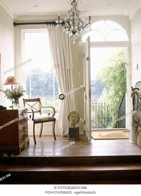 Traditional white hall with open front door
