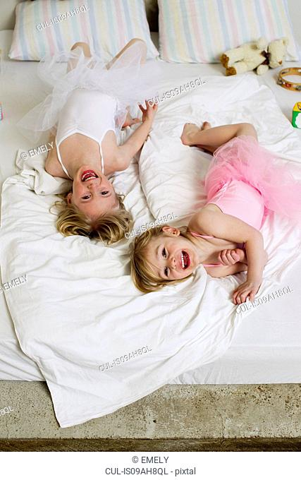 Portrait of two young sisters playing on bed