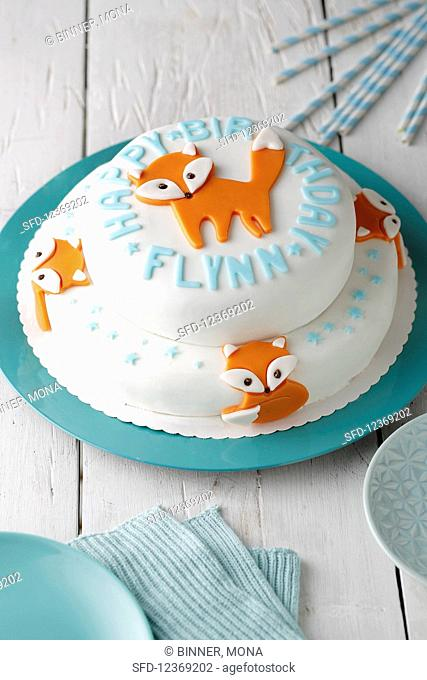 Two-storey birthday cake with white fondant glaze and orange foxes