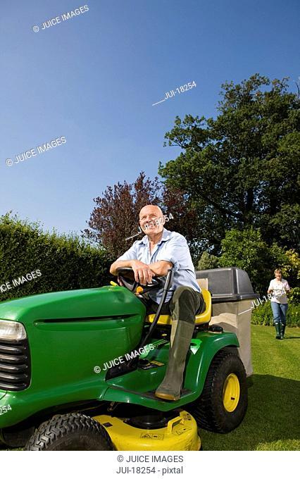 Senior man sitting on riding lawn mower