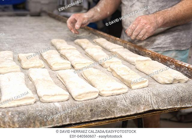 Baker preparing uncooked bread dough loaves ready to bake