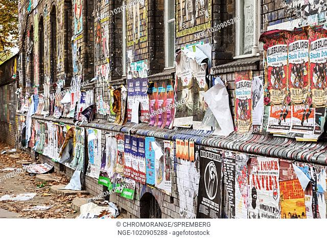 House wall spotted with posters in Berlin s Friedrichshain district