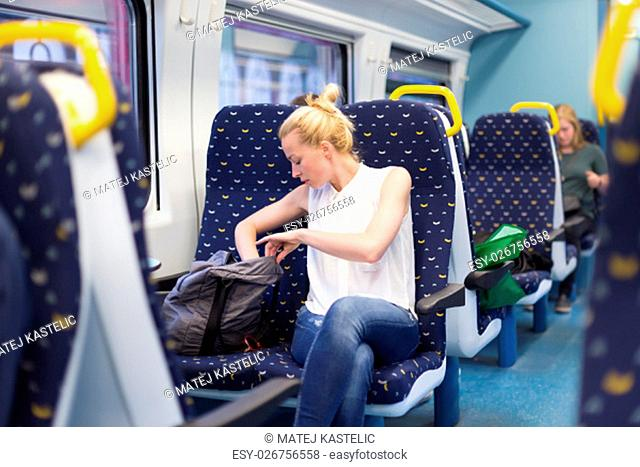 Young woman searching something in her bag while traveling by train