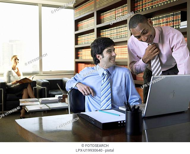 Businessmen using laptop computer in library