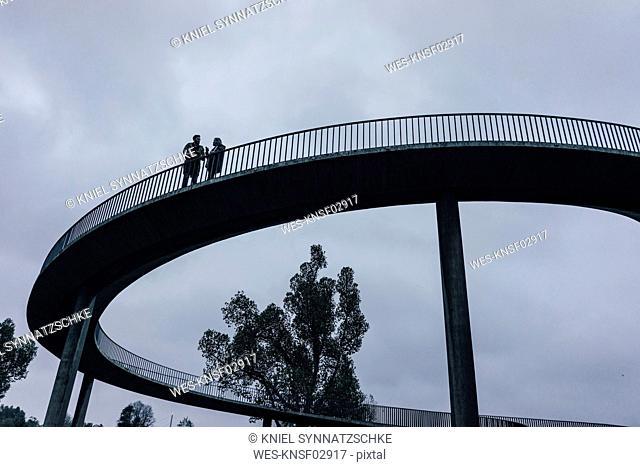 Two businessmen standing on dark bridge, having a meeting
