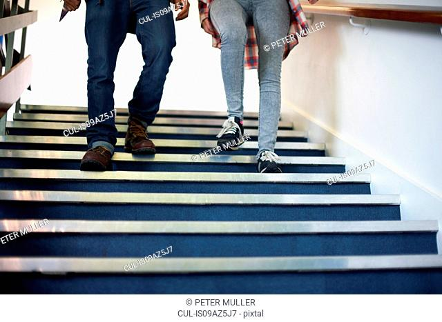 Waist down view of male and female college students moving down stairway