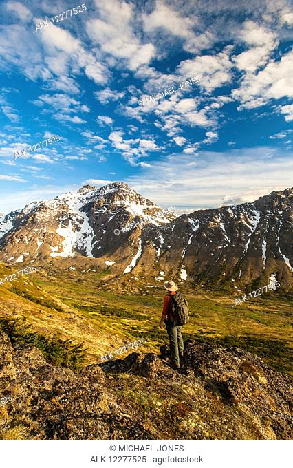 Hiker on rock outcrop overlooks Powerline Pass valley and trail, Chugach State Park, Southcentral Alaska