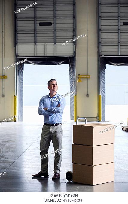 Caucasian businessman standing near cardboard boxes in warehouse