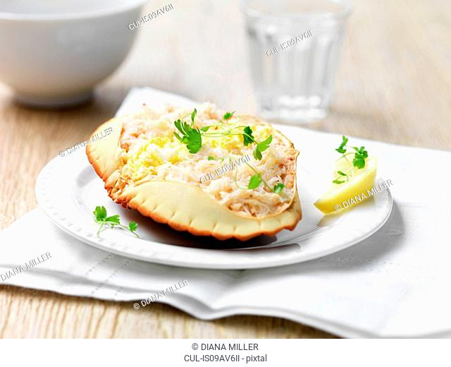 Orkney crab in shell with herbs and lemon wedge