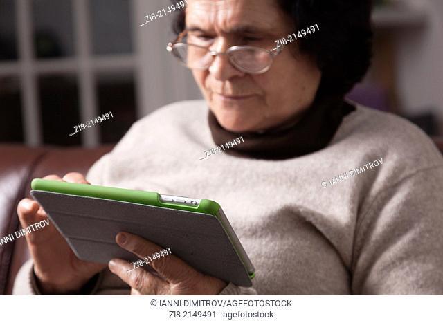 Senior woman reading on a tablet
