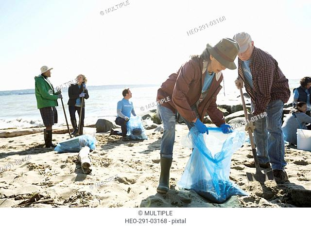 Beach cleanup volunteers digging on sunny beach