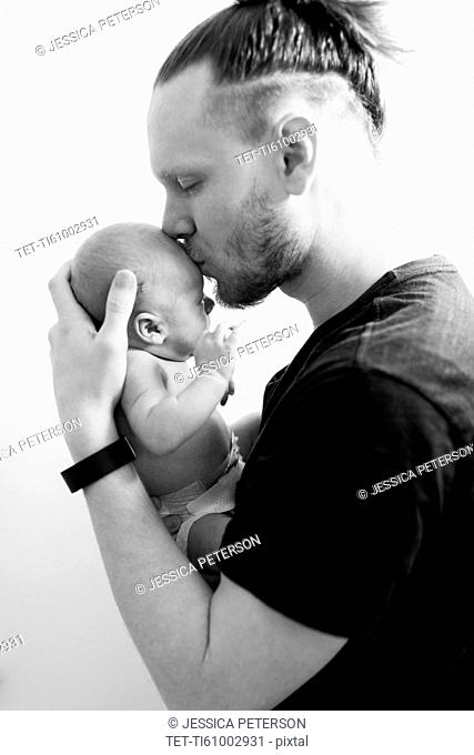 Father kissing newborn son (0-1 months)