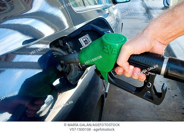 Man's hand holding gas pistol, refuelling at a gas station. Close view