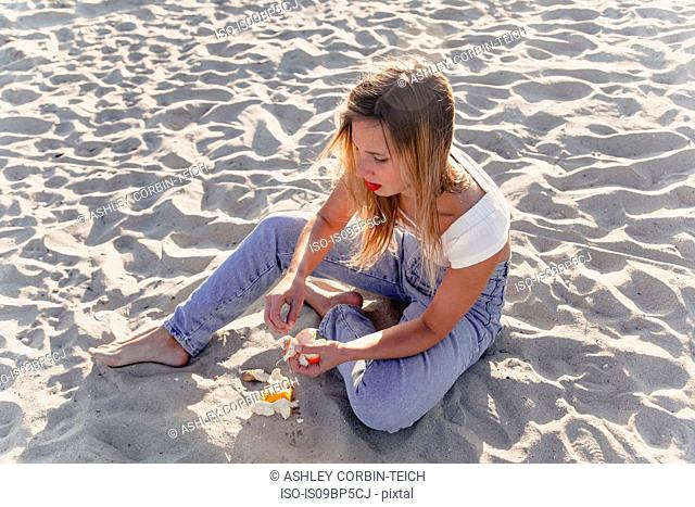 Young woman peeling fruit on beach