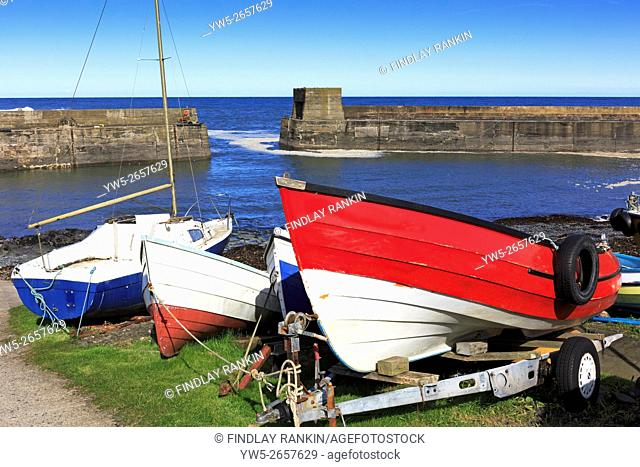 Three small fishing boats beached at the side of Craster harbour, Northumberland, England, UK