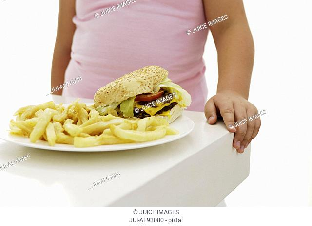 Hamburger and french fries in front of overweight girl