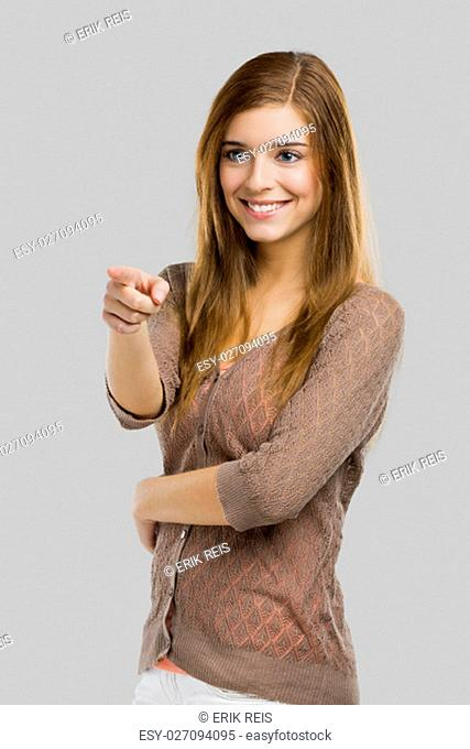 Beautiful blonde woman pointing somewhere, isolated over a gray background