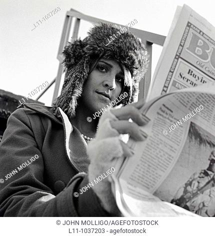 Woman looking around the side of her newpaper