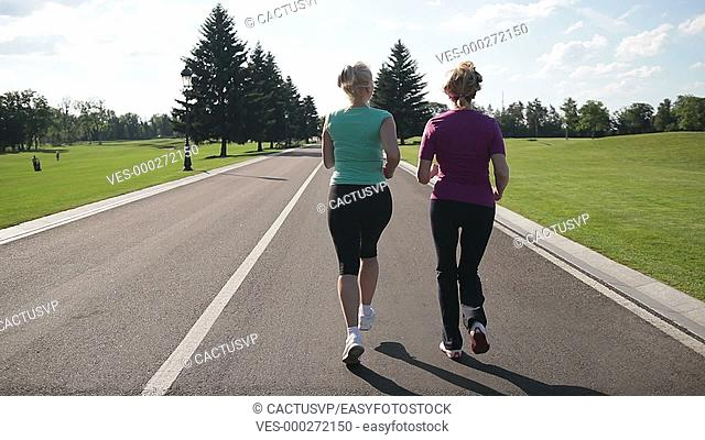 Back view of running women jogging in the park