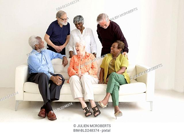 Older people laughing on sofa