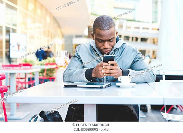 Young man sitting outside cafe, using smartphone