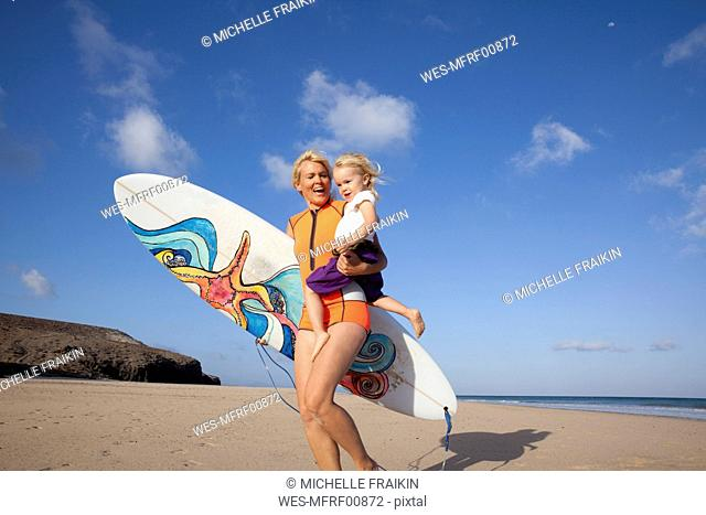 Spain, Fuerteventura, happy mother and daughter walking with surfboard on the beach