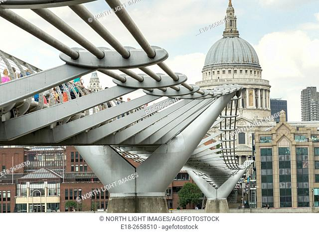 UK, England, London. Low angle view of the Millennium pedestrian Bridge crossing the Thames River, with the dome of Saint Paul's Cathedral in the distance