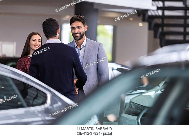 Car salesman greeting, shaking hands with couple customers in car dealership showroom