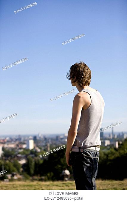 A young man in a park looking across the city