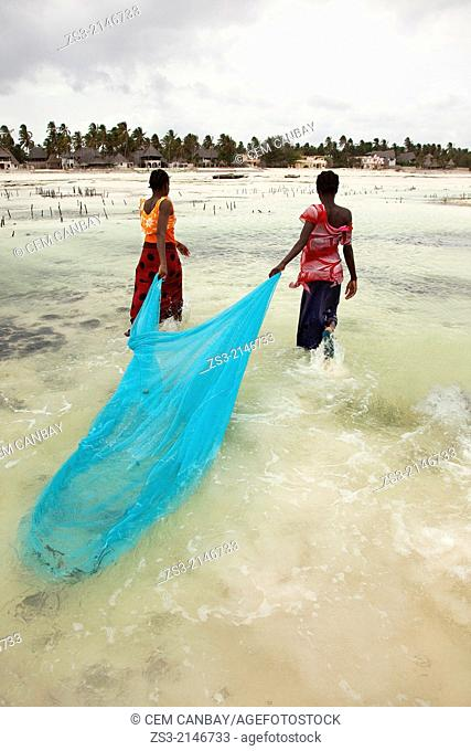Young muslim girls in colorful dress with fishnet on Jambiani beach, Zanzibar Island, Tanzania, Indian Ocean, East Africa