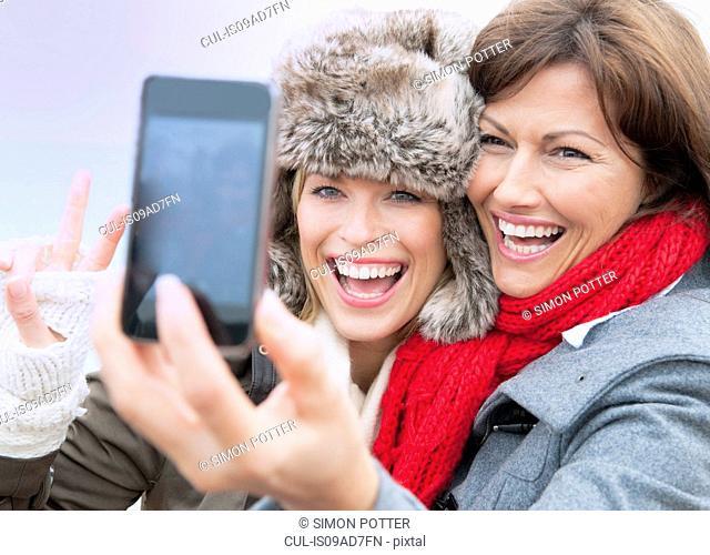 Two female friends taking self portrait at coast, Thurlestone, Devon, UK