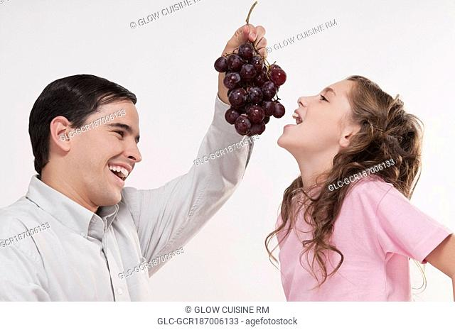 Man eating grapes to her daughter
