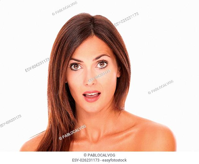 Front view portrait of surprised latin woman with nude shoulders looking at camera on isolated white background