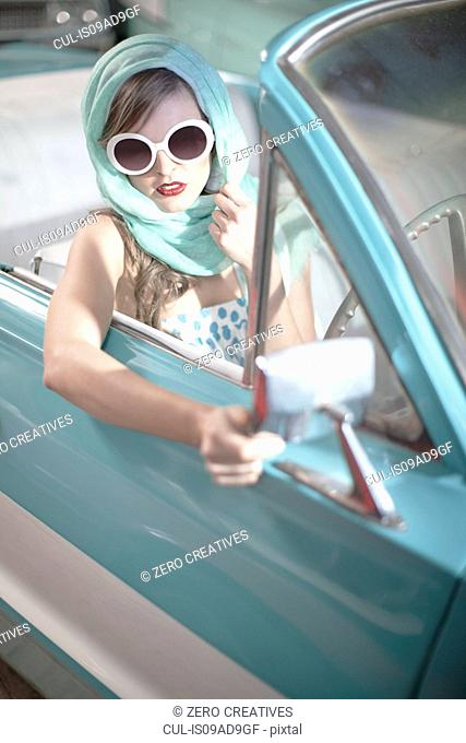 Woman in headscarf and white sunglasses in vintage convertible
