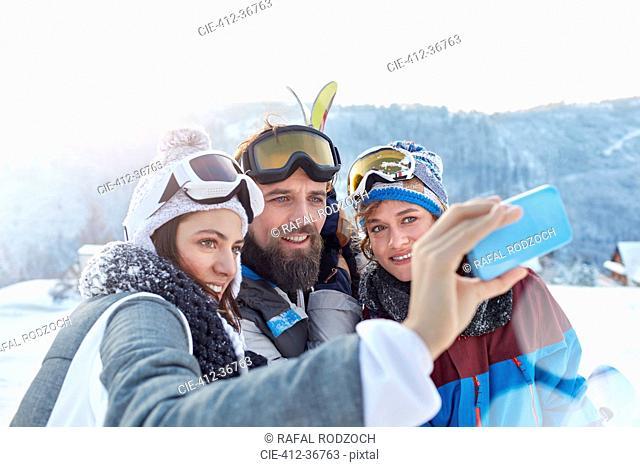 Skier friends taking selfie with camera phone in snowy field