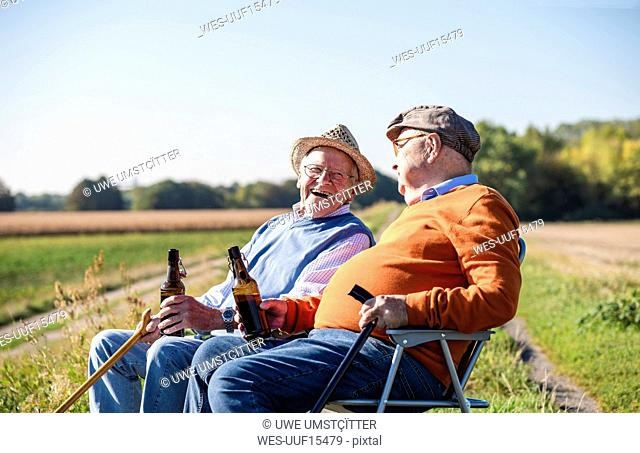 Two old friends sitting in the fields, drinking beer, talking about old times