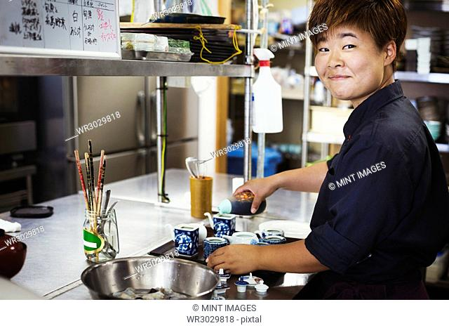 Waitress working in the kitchen of a Japanese sushi restaurant, smiling at camera