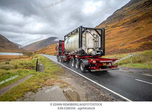 A truck drives on a road near Three Sisters of Glen Coe in Glen Coe, Scotland