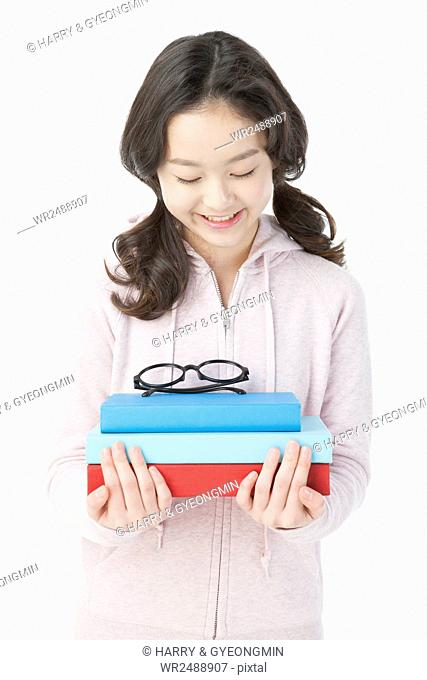 Portrait of smiling school girl in casual clothes holding books and glasses looking down