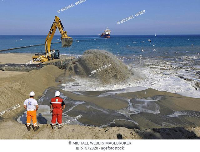 Dredger pumping sand through a hose onto a beach for beach nourishment or beach replenishment, Platja de Barceloneta, Barcelona, Catalonia, Spain, Europe
