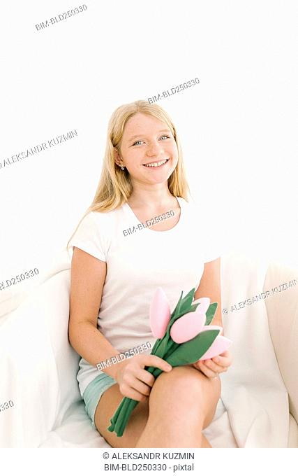 Portrait of smiling Middle Eastern girl holding toy flowers