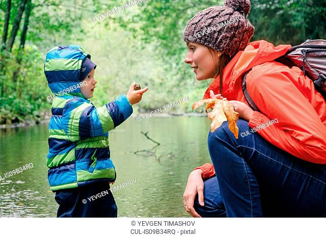 Mother and son exploring stream in forest, Vancouver, British Columbia, Canada