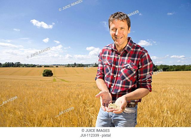 Portrait smiling farmer examining sunny rural barley crop field in summer