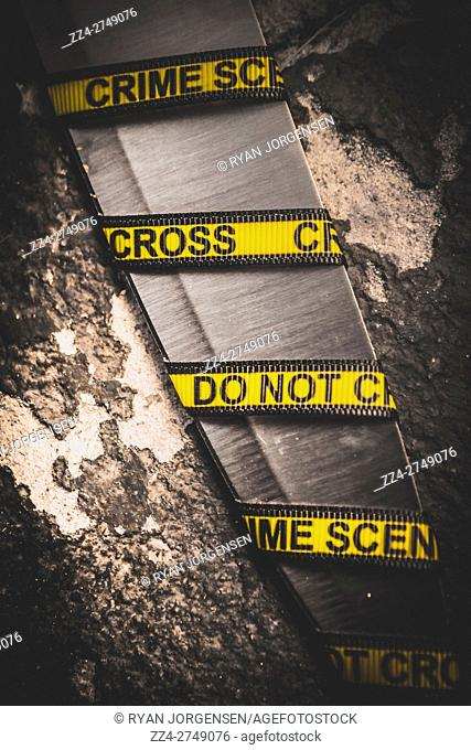 Crime scene closeup details on a knife blade wrapped in yellow crime scene tape. Investigation clues