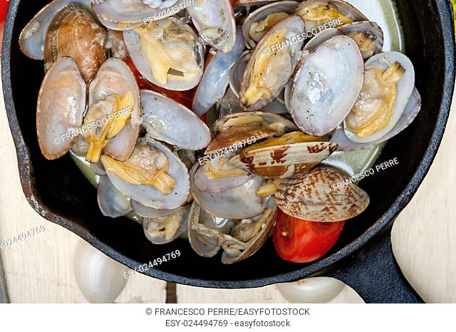 fresh clams stewed on an iron skillet over wite rustic wood table