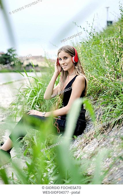 Smiling teenage girl wearing headphones listening to music at the riverside