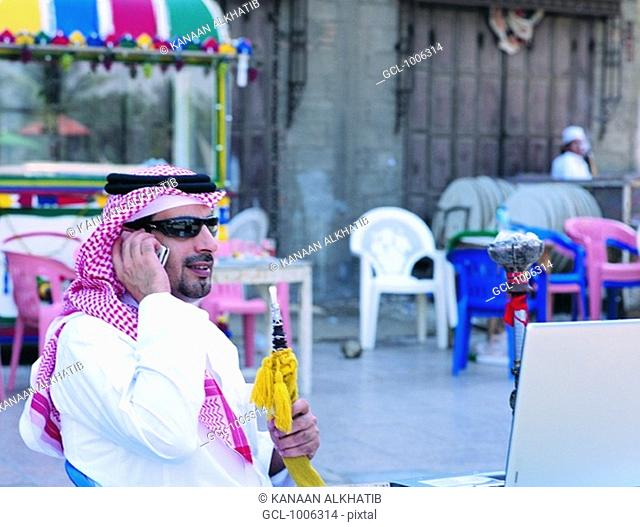 Saudi businessman using mobile phone and laptop in Old Town of Jeddah, Saudi Arabia