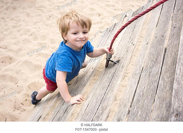 High angle view of smiling boy holding rope at playground