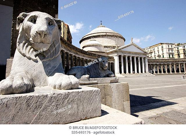 Stone carved lions on the Piazza del Plebiscito with Church of San Francesco di Paola in the background. Naples. Campania. Italy
